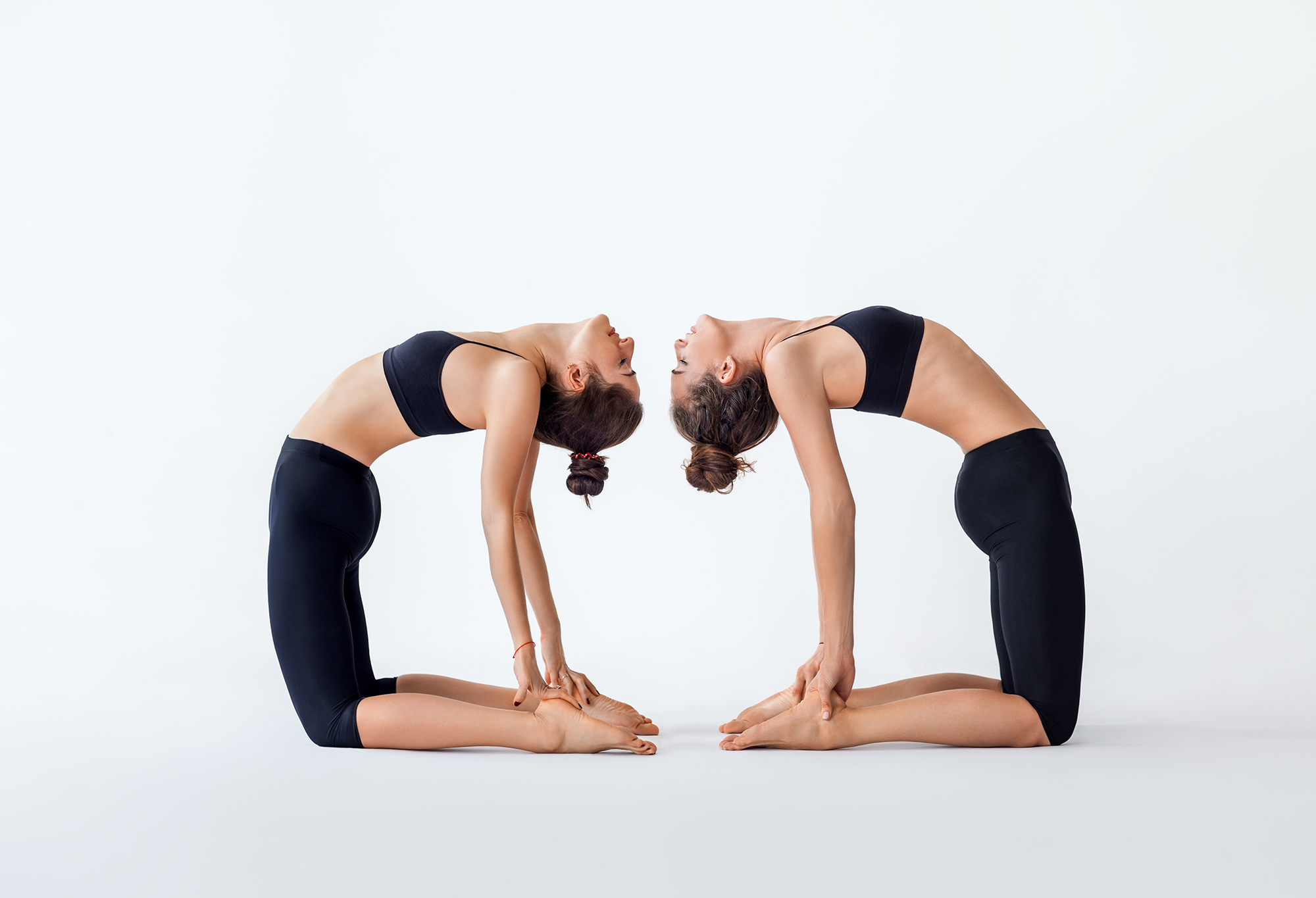 Two young women doing yoga asana camel pose. Ustrasana