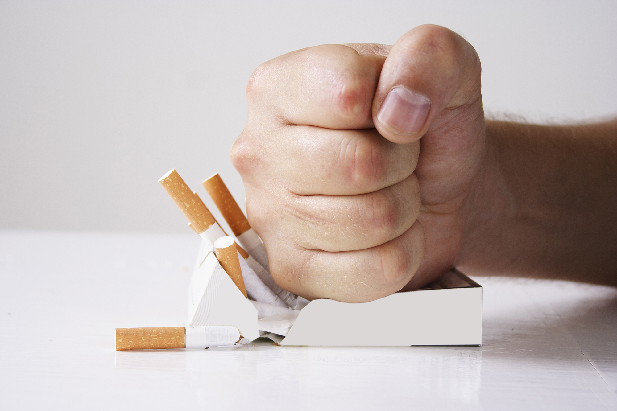 Hand crushing cigarettes over white background